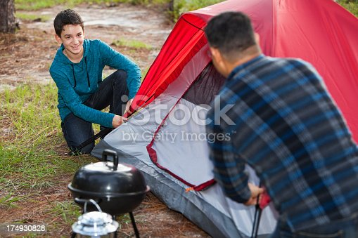 Hispanic father (40s), and son (10 years) camping, pitching the tent.  Focus on boy.