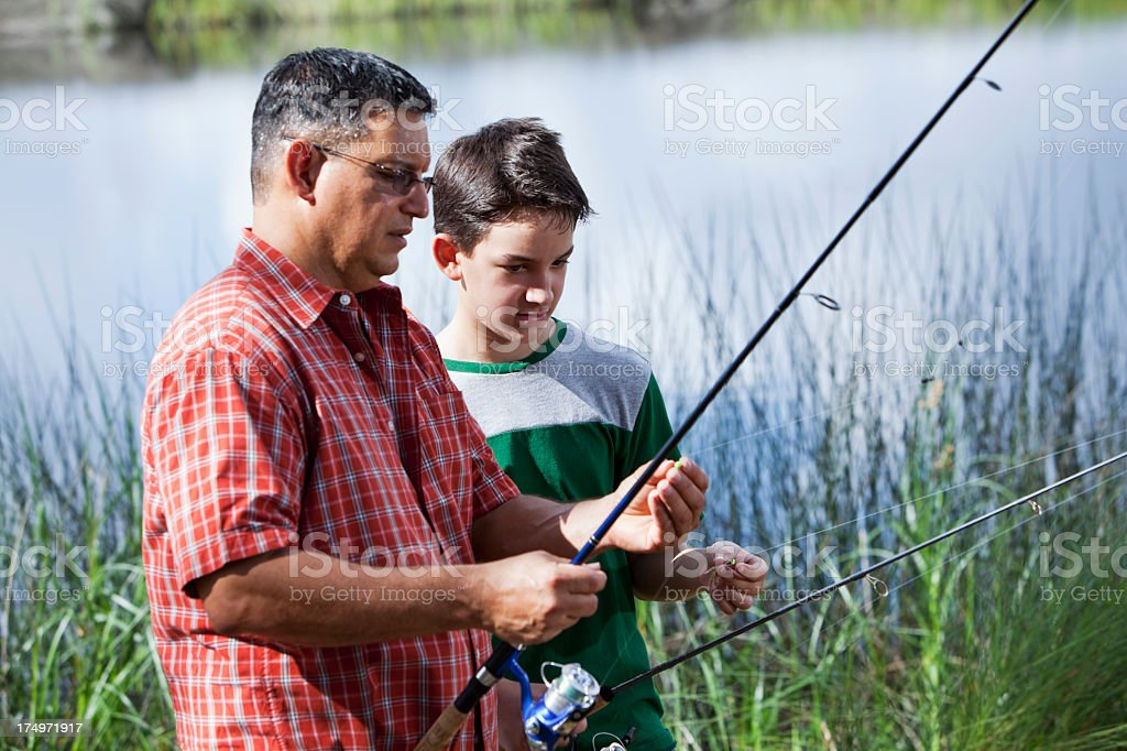 Hispanic father and son fishing stock photo