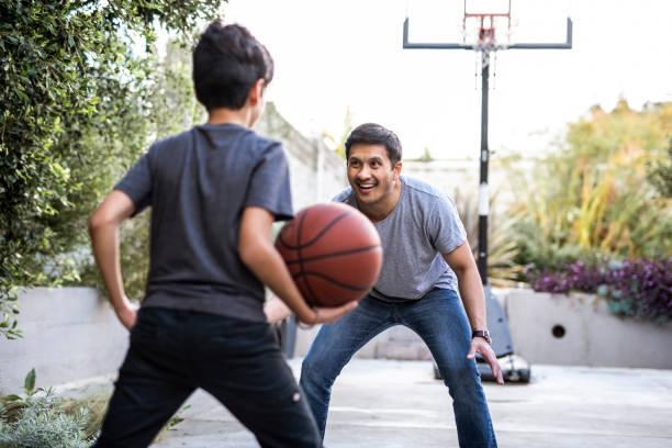 Hispanischer Vater und Sohn spielen Basketball im Hinterhof – Foto