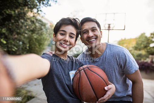 Hispanic father and son taking a selfie outdoors whilst playing basketball