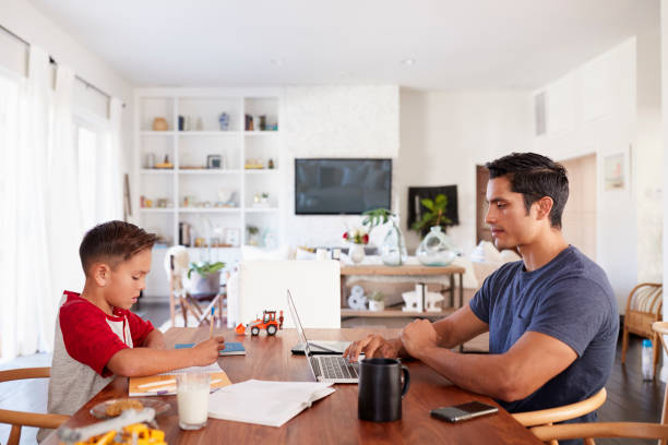 hispanic father and son working opposite each other at the dining room table, side view, close up - work from home stock pictures, royalty-free photos & images