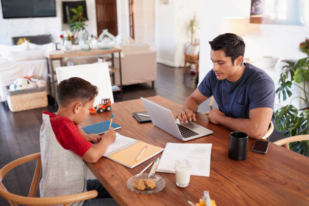Hispanic father and son working opposite each other at the dining room table, elevated view Hispanic father and son working opposite each other at the dining room table, elevated view monkeybusinessimages stock pictures, royalty-free photos & images
