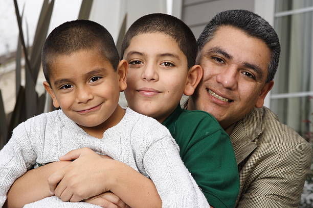 hispanic father and sons in front of house stock photo