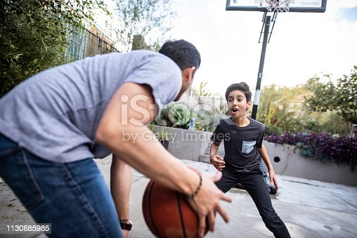 Hispanic father dribbling the basketball ball whilst playing with his son