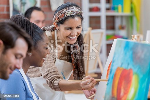 Beautiful mature Hispanic female artist works with African American female art student. The artist is helping the woman with a painting.