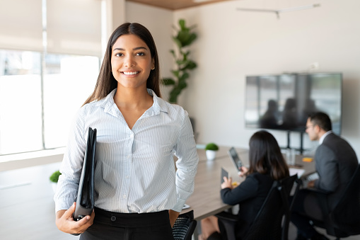 Portrait of hispanic businesswoman with a file standing in meeting room with colleagues disucssing in background