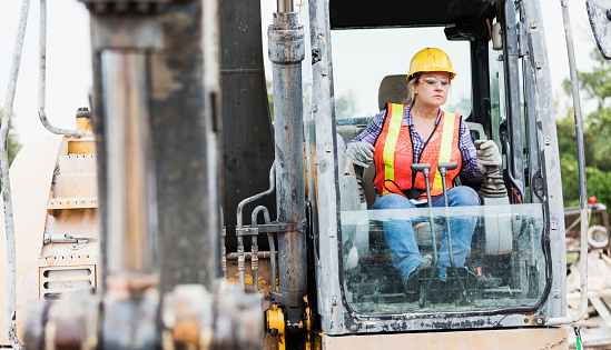 A mature Hispanic woman in her 40s working at a construction site, operating an earth mover. She is wearing a hardhat, reflective vest, and safety goggles.