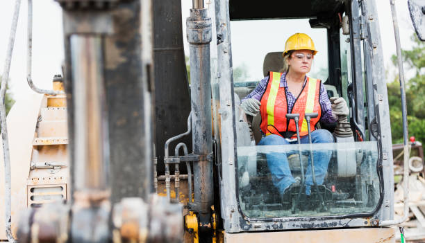 Hispanic female construction worker driving earth mover stock photo
