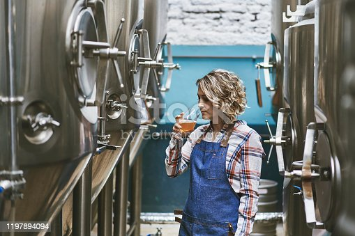 istock Hispanic Female Craft Brewer Examining Beer Sample 1197894094