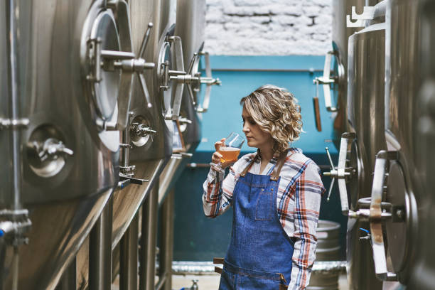 Hispanic Female Craft Brewer Examining Beer Sample stock photo