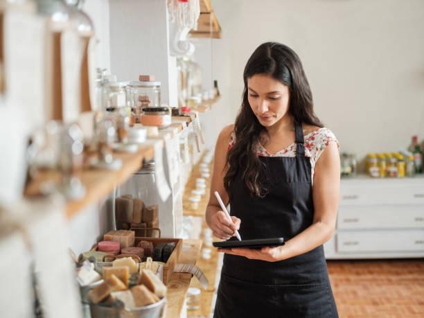 Hispanic female employee making inventory in sustainable shop stock photo