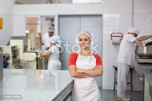 Close-up of young female supervisor leaning against commercial kitchen island in Argentine pasta factory while coworkers operate machinery in background.