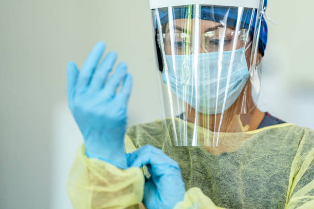 Hispanic female medical professional in Personal Protective Equipment Close up of a female doctor wearing personal protective equipment (PPE) during the COVID-19 outbreak to protect from the transfer of germs. protective workwear stock pictures, royalty-free photos & images