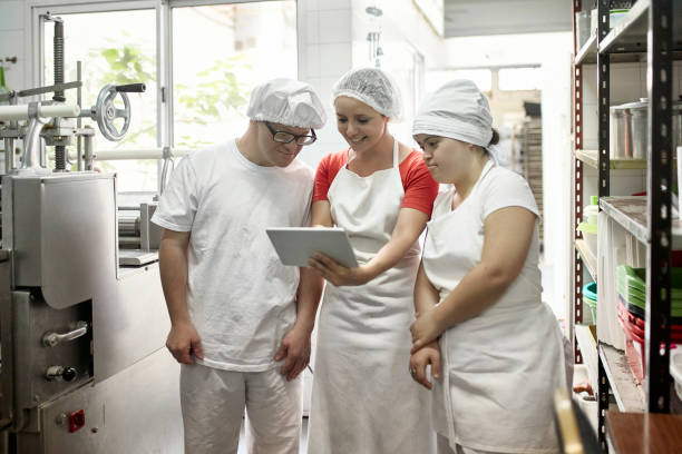 Hispanic Female Supervisor Advising Factory Coworkers stock photo
