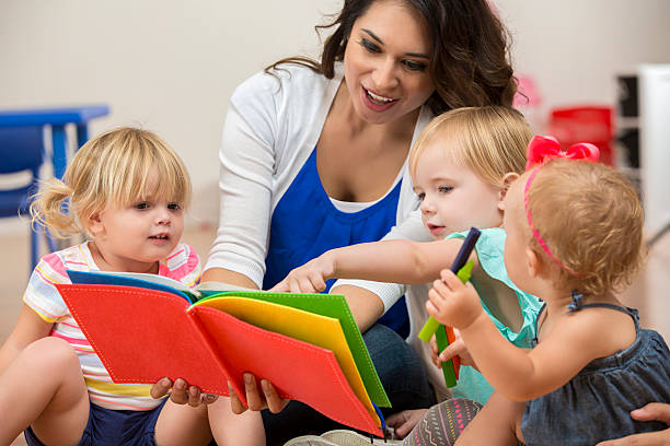 Hispanic female teacher reading a book to cute preschool students stock photo