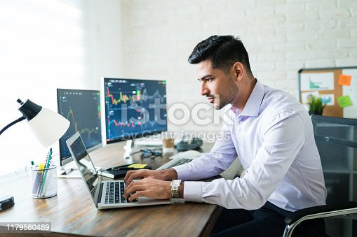 Handsome Latin freelance broker trading through laptop at desk while working from home