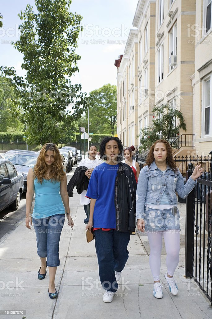 Hispanic friends walking towards the camera royalty-free stock photo