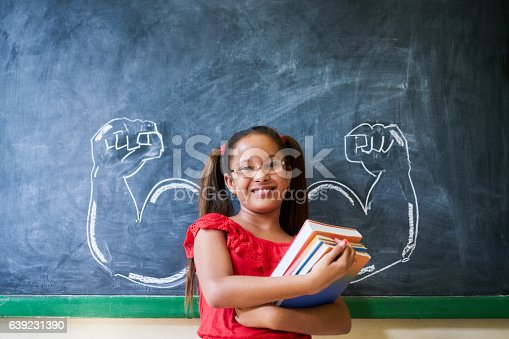 istock Hispanic Girl Holding Books In Classroom And Smiling 639231390