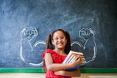 Concept on blackboard at school. Intelligent and successful hispanic girl in class. Portrait of female child smiling, looking at camera, holding books against drawing of muscles on blackboard