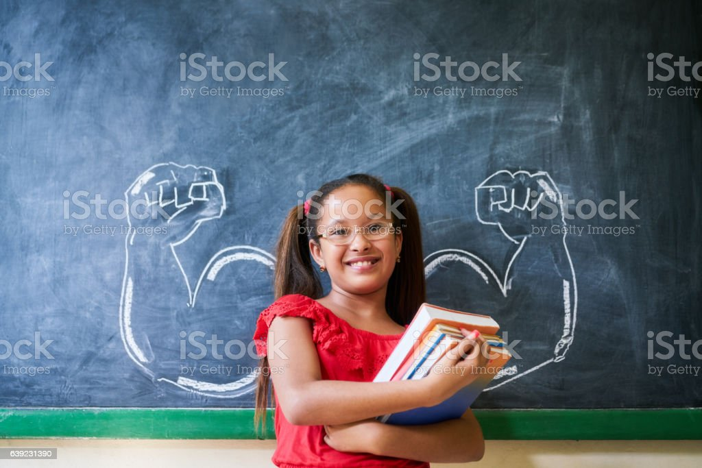 Hispanic Girl Holding Books In Classroom And Smiling stock photo