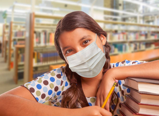 Hispanic Girl Student Wearing Face Mask Studying in Library stock photo