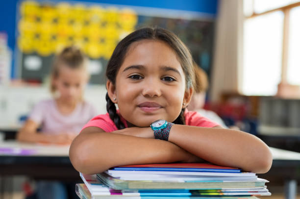 Hispanic girl with chin on books Portrait of cute little schoolgirl leaning on stacked books in classroom. Happy young latin girl in casual keeping chin on notebooks. Closeup face of smiling girl at elementary school. 8 9 years stock pictures, royalty-free photos & images