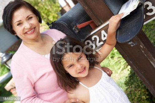 istock Hispanic Grandmother And Granddaughter Checking Mailbox 184402929