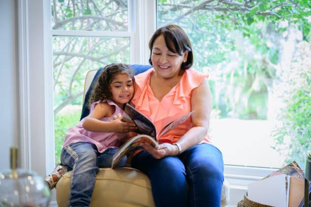 Hispanic grandmother and granddaughter enjoying picture book stock photo