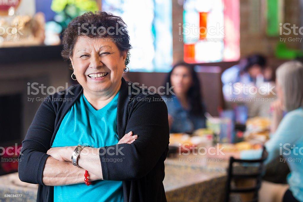 Hispanic abuela sonriente en un restaurante de propiedad familiar restaurante foto de stock libre de derechos