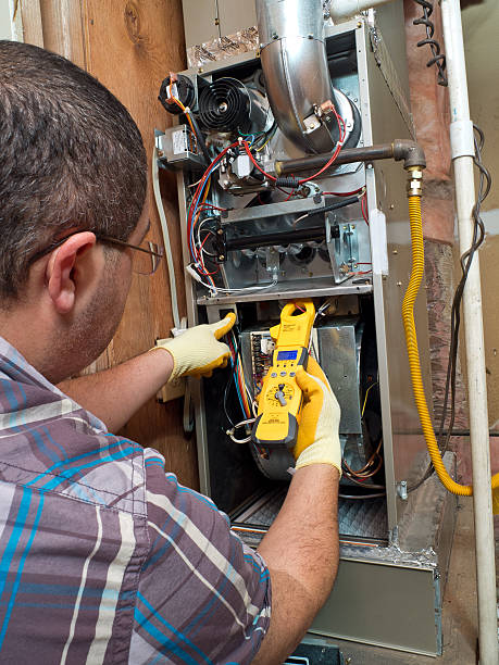 hispanic handyman repairman conducting residential hvac repair - furnace stock photos and pictures