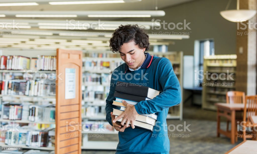Hispanic High School Student Carrying Stack Of Books Stock Photo Download Image Now Istock