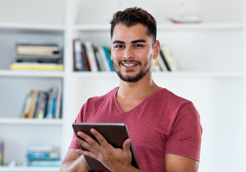 istock Hispanic hipster man online with digital tablet 1182592065