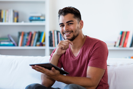 istock Hispanic hipster man reading news with tablet 1182591960