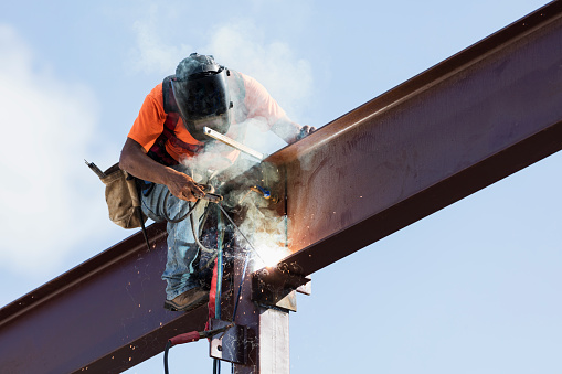 An Hispanic steel worker working high up on a girder. He is sitting on the girder, wearing a safety harness, welding to secure the girder to a column.