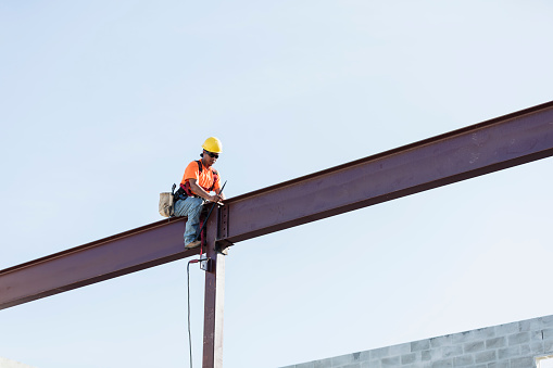 An Hispanic steel worker working high up on a girder. He is sitting on the girder, wearing a safety harness, working to secure the girder to a column.