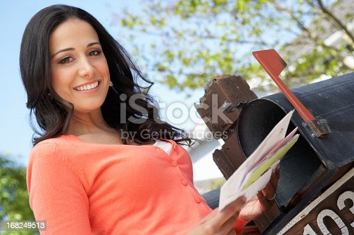 istock Hispanic lady smiling as she checks her mailbox and letters 168249513
