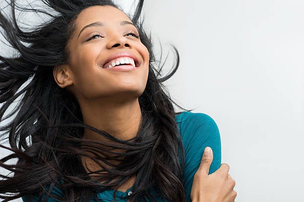 Hispanic lady with long black hair smiling happily Closeup of smiling young woman with hair in the wind straight hair stock pictures, royalty-free photos & images