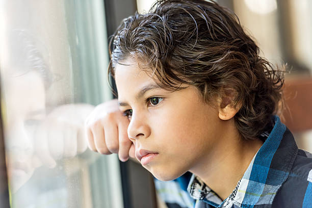 hispanic little boy - boy looking out window stock pictures, royalty-free photos & images