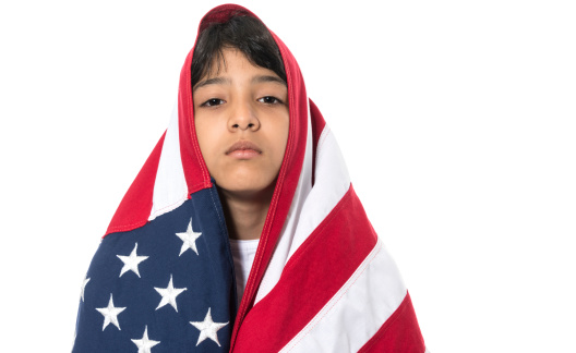 Hispanic little girl posing wrapped in the US flag in white background