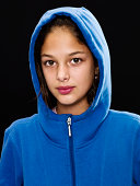 Ten years old hispanic little girl posing looking at the camera wearing a hoodie on black background (this picture has been shot with a super high definition Hasselblad HD3 II 31 megapixels camera)