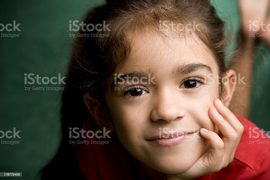 Hispanic Little Girl Smiling With Chin on Hand royalty-free stock photo