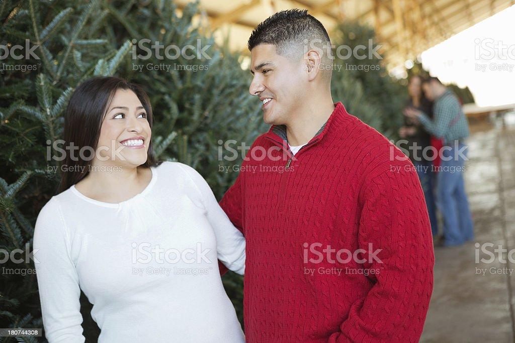 Hispanic lovers Christmas tree shopping together royalty-free stock photo