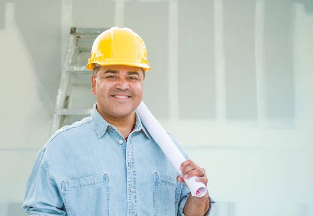 Hispanic Male Contractor mit Blueprint-Pläne tragen harten Hut vor Trockenbau und Leiter – Foto