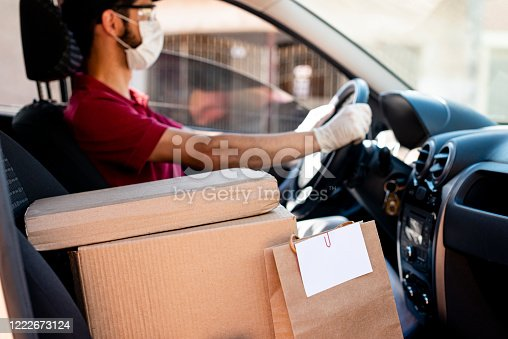 Hispanic male courier with orders in car. Food delivery service.