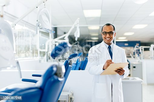 A hispanic male dentist standing in a dental clinic with documents in his hands, looking at the camera and smiling