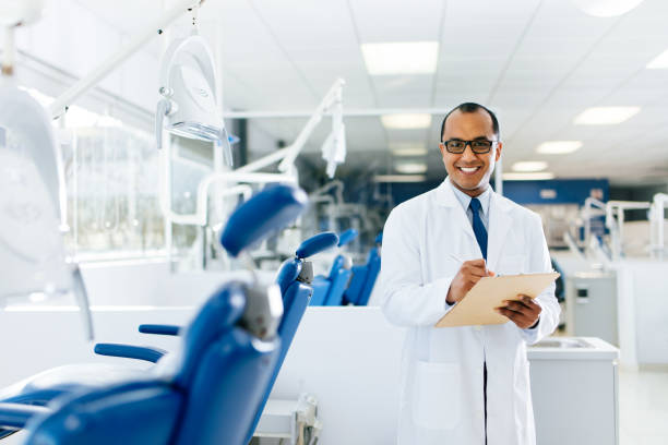 Hispanic male dentist standing in clinic and looking at camera stock photo