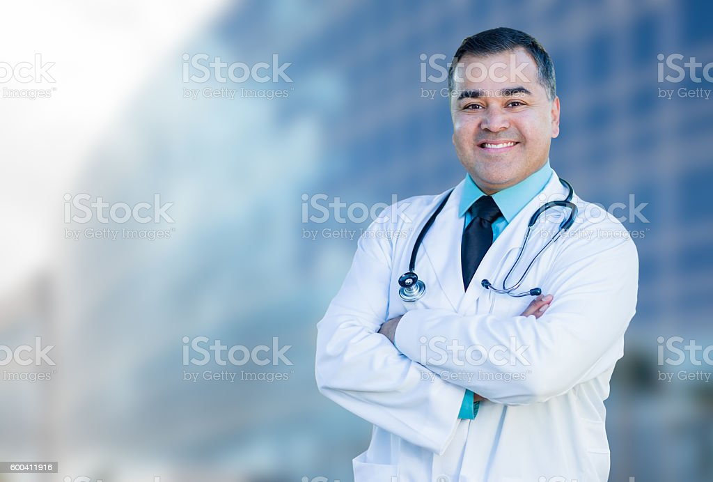 Hispanic Male Doctor or Nurse In Front Of Hospital Building stock photo