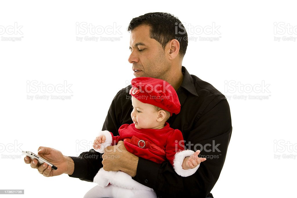 Hispanic male father holding infant girl dressed in santa suit royalty-free stock photo