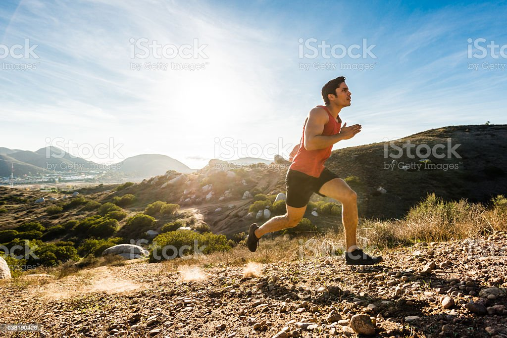 Hispanic Male Running Up A Steep Hill In The Mountains stock photo