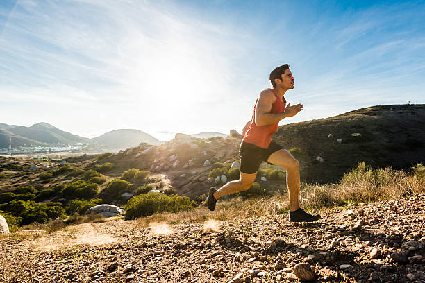 hispanic male running up a steep hill in the mountains - jogging hill bildbanksfoton och bilder